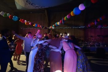 Bride and her friends having a group hug on the dancefloor at Izzy & Alex's Wedding in their Private Barn in Feock, September 2015