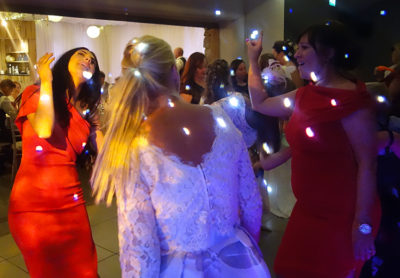 Guests on the dancefloor. This image features three women dancing together. A woman in the centre is seen from the back wearing a white lace dress with her blonde hair swinging in a ponytail. To either side of her are two guests facing the camera weearing scarlet close fitting dresses with their hands in the air and their heads thrown back. They are lit with R2 events 'white dots' disco lights.