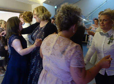 Friends and family join Lianne and Rachel on the dancefloor after their first dance. The image shows guests smiling and dancing in pairs