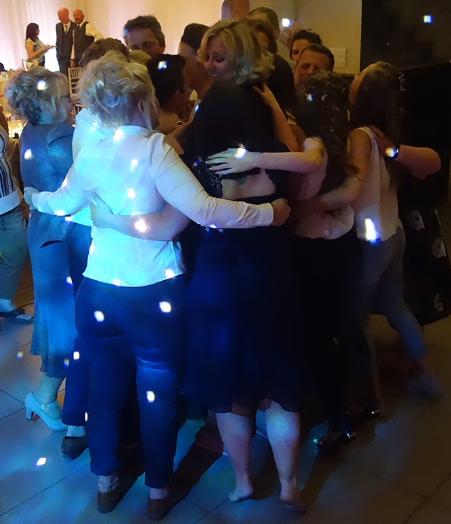 Lianne and Rachel's friends and family join them on the dancefloor at the end of the night for a big group hug. The image shows a tight knit group from the back with their arms around each other.