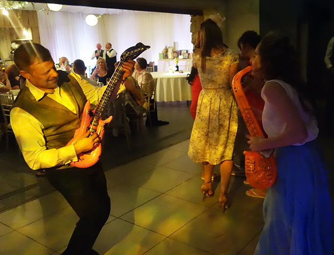 Two wedding guests, a man on the left and a young woman on the right, play inflatable instruments to each other; the man plays a guitar and the girl is 'blowing' into a saxaphone. The floor is lit up with a yellowish R2 Events wash light.