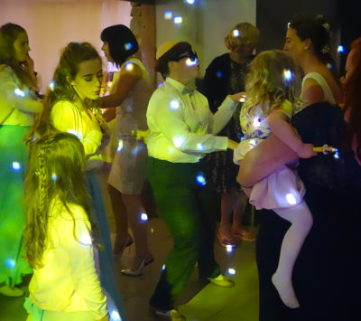 This picture shows a large group of guests on the dancefloor. Lianne is on the right of the picture and a woman is standing beside her with a child on her hip. Rachael is in the centre of the picture wearing dark trousers, a white shirt, dark sunglasses and a wig on her head! The wig is styled like a monk's head with a bald top and a circle of hair below. To the left of the picture there are a few younger guests enjoying the music.