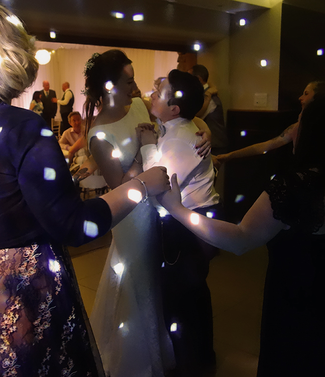 Brides Lianne and Rachel are dancing close to each other, smiling and gazing into each other's eyes in the centre of a circle of guests, holding hands. The scene is lit up with R2 Events 'white dot's' disco lights.