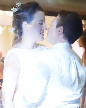 A portrait of the brides of a same sex wedding captured in an intimate moment on the dance-floor. The photo shows the couple from the waist up, both wearing white and gazing into each other's eyes, about to kiss.