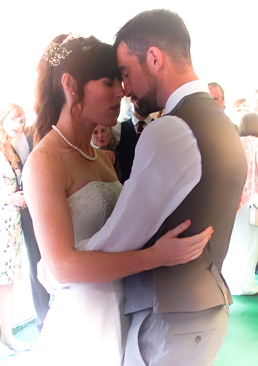 2/3 portrait of bride and groom Kate and Steve's first dance. They're in a romantic embrace with their foreheads together, eyes closed, with their arms around each other's waist. The couple are wearing traditional wedding attire and Kate has her long dark hair loosely tied up.