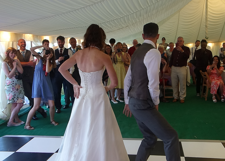 Marquee wedding reception, the couple begin their first dance...with a difference. The couple are seen from behind, in formal wedding attire, doing a 'robot' dance!