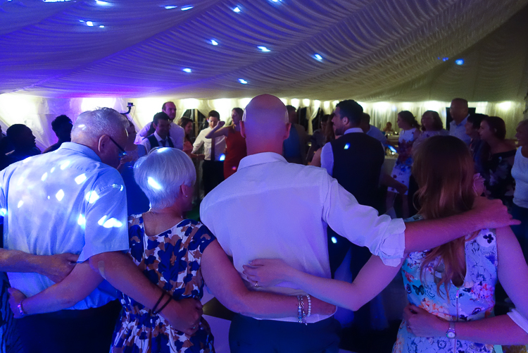 Guests at a marquee wedding join arms and in a circle and sway to R2 Events music. (Guests photographed from behind with interlaced arms._