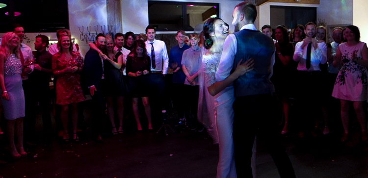 Ben and Harriet's First Dance is lit up with soft R2 events water-lights and the wedding guests are stood around the edge of the room watching the couple dancing in an embrace. The bride is looking into the groom's eyes with a big smile on her face.