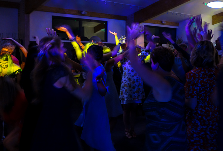 Ben and Harriet's wedding guests get together on the dancefloor under R2 Events' yellow disco lights, which spotlight hands in the air and one of the guest's faces. Guests are laughing and singing and virtually everyone has their hands in the air.