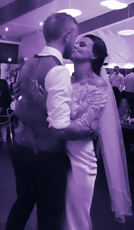 Ben and Harriet's wedding day. This photo shows a close up of the couple in black and white. They're standing kissing in a romantic embrace, seen from side on. The bride is wearing a fitted white dress with a long tulle veil and the groom is wearing formal attire in a waistcoat with his white shirtsleeves rolled up.