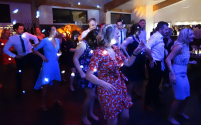 Ben and Harriet's wedding guests get on the dancefloor for the Macerana. This colourful photo shows men and women in rows with their hands on their hips. In the front row is a woman in a knee-length patterned red dress with a frill around the hem that seems to shake with the music. The scene is lit up with white dots from R2 Event's dicso lights.
